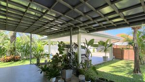 A large covered area, the carport for 2 cars and stretches of garden