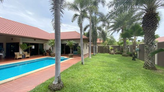 A nice pool and juicy lawns with palm-trees