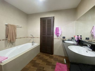The master-bathroom has a bathtub and a shower cubicle