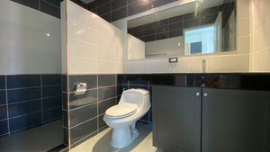 The modern bathrooms are tiled to the ceiling
