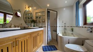 This bathroom has a double-sink and a bathtub plus shower cabin